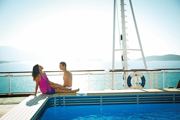 Couple lounging by the pool on the sun deck of their cruise ship