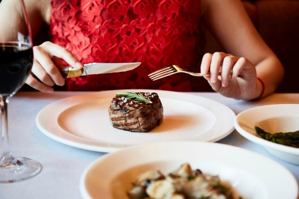 A guest eating a steak dish in Chops Grille on Sky Princess