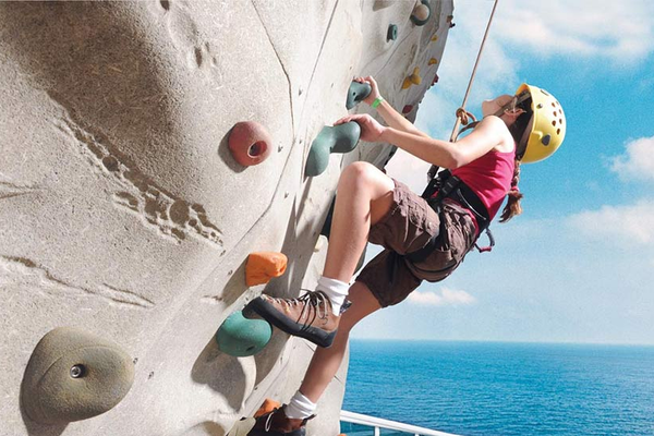 Guest climbing the rock climbing wall on-board Grandeur of the Seas